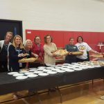 Teachers serving pizza.